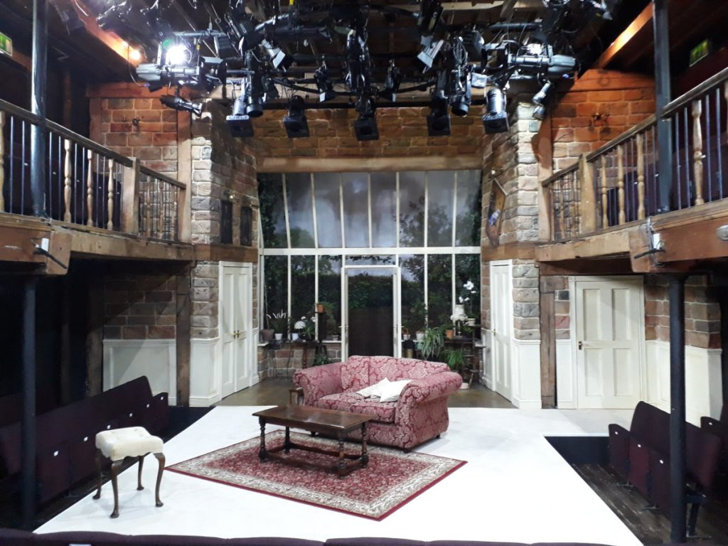 House set – dressed and under working lights designed by Neil Irish at The Watermill Theatre